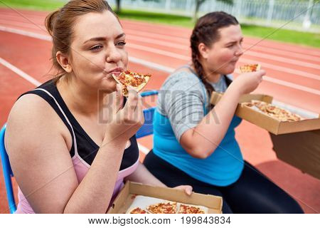 Hungry over-sized females eating pizza after workout on stadium