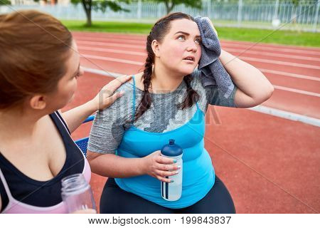 Unhappy and sweaty over-sized female drying her face with towel while another woman encouraging her during refreshment