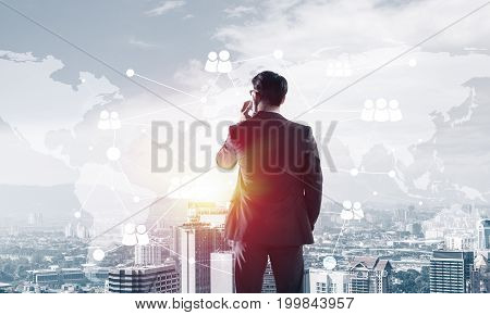 Elegant businessman standing with back and talking his mobile phone