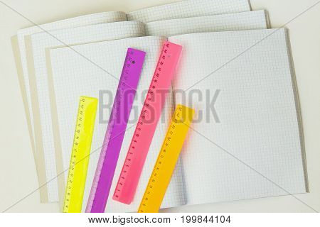 Close-up of a set of colored rulers on a background of large open empty and blank notebooks in a cage, top view, texture. Place for text, the concept of starting school and any new cases
