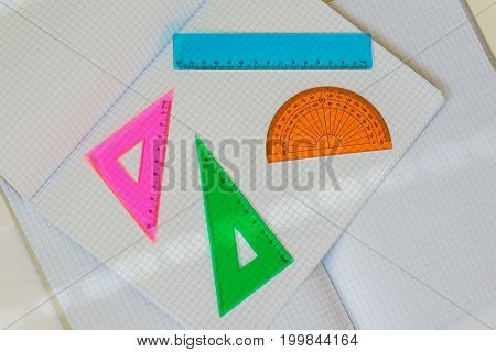 Close-up of a set of colored instruments for geometry on a background of large open empty notebooks in a cage, top view, texture. Place for text, concept of starting school, back to school, any new cases