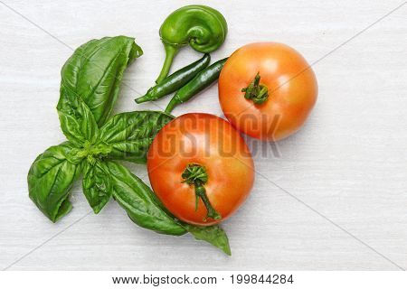 Freshly harvested large red tomatoes with basil leaves and green hot peppers