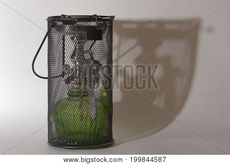 hookah with green glass flask with coal tongs in carrying case of steel mesh casts characteristic shadow