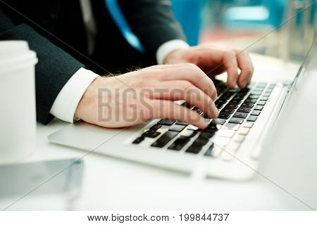 Hands of stock trader typing on laptop by workplace