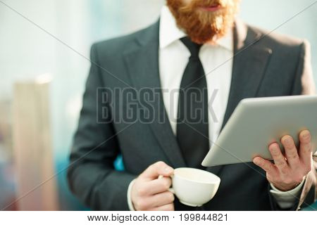 Stock broker with tablet and cup of tea reading online data