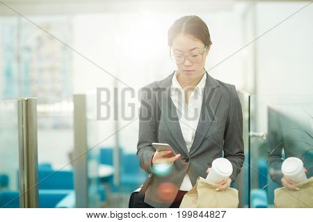 Businesswoman with drink and paper packet messaging in smartphone while waiting for colleague