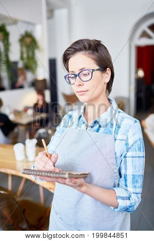 Portrait shot of confident middle-aged waitress in eyeglasses taking notes while standing at cozy small cafe, blurred background