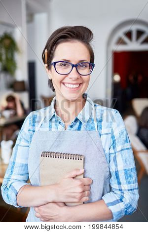 Attractive waitress in eyeglasses looking at camera with charming smile while working at fashionable restaurant, waist-up portrait