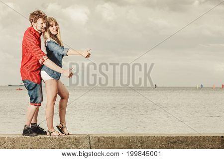 Young Couple Thumbing And Hitch Hiking By Seaside