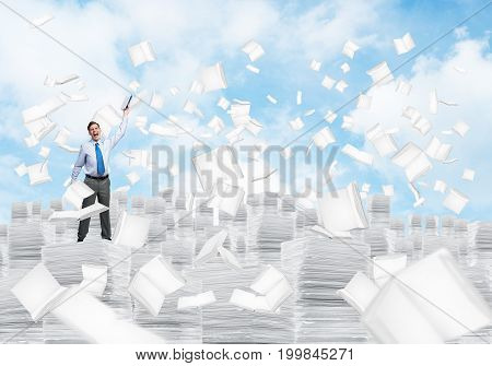 Businessman keeping hand with book up while standing among flying books with cloudly skyscape on background. Mixed media.