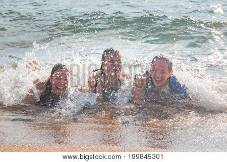 Beautiful Young Girls Lay on the Sand While Waves Splash Over Them at the Beach
