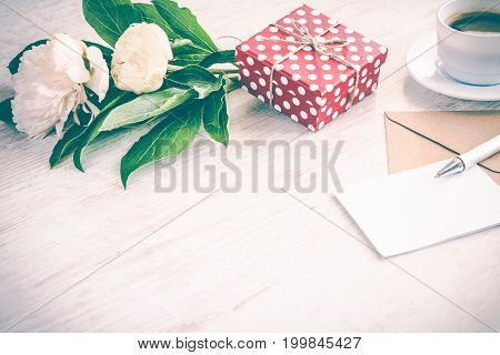 Red dotted gift box kraft envelope and empty greeting card coffee cup and peony flowers bouquet over white wood background. Copy space. Vintage effect.