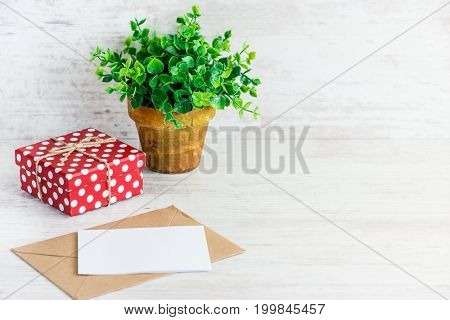 Red dotted gift box empty card kraft envelope and a green flower in a rustic ceramic pot. White wooden background copy space.