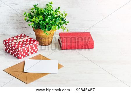 Red dotted gift box empty card kraft envelope red book and a green flower in a rustic ceramic pot. White wooden background copy space.