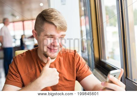 technology, communication and people concept - Young man holding a smart phone with thumbs up.