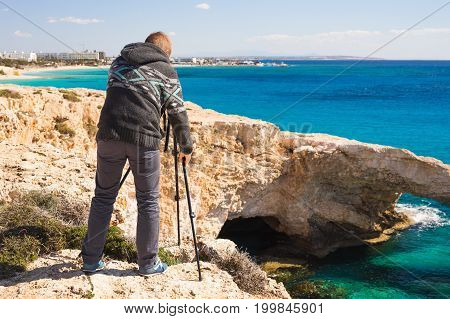 Travel, vacation, photographer and hitchhiker concept - traveler man photographed mountains and city in the smartphone