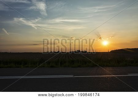 Evening landscape. Sunset in a field in the clouds