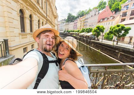 Happy young couple in love takes selfie portrait in Karlovy Vary in Czech Republic. Pretty tourists make funny photos for travel blog in Europe