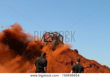 Blue Sky With Red Car Spinning Over Steep Sand Mountain