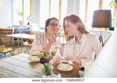 Pretty middle-aged manager in eyeglasses sharing gossip with colleague while they spending coffee break at lovely restaurant with panoramic windows
