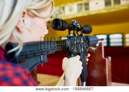 Girl with rifle aiming at target during shooting practice