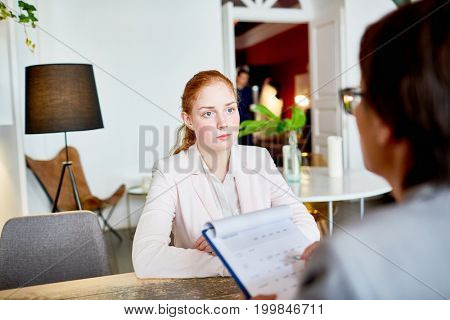 Over shoulder view of pretty red-haired applicant for position listening to HR manager with concentration while participate in interview at fashionable restaurant