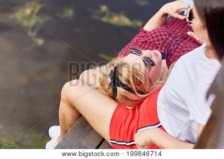 Restful girlfriends relaxing on bench in park on summer day