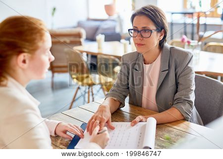 Completion of successful negotiations: confident middle-aged entrepreneur passing contract for signature to her business partner while they sitting at cozy coffeehouse