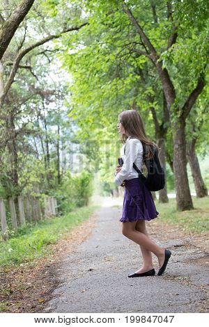 Pretty Beautiful Blonde School Girl Child With Glasses, White Shirt, Purple Skirt And Backpack Holdi