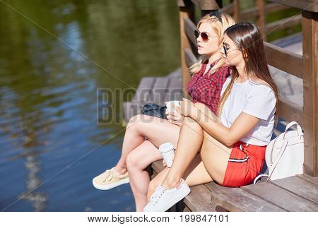 Two young females with drinks sitting on wooden pontoon by water