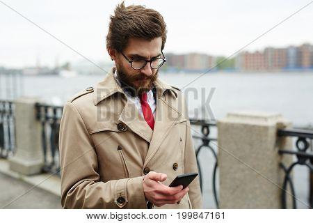 Elegant man in beige trenchcoat got sms from business partner