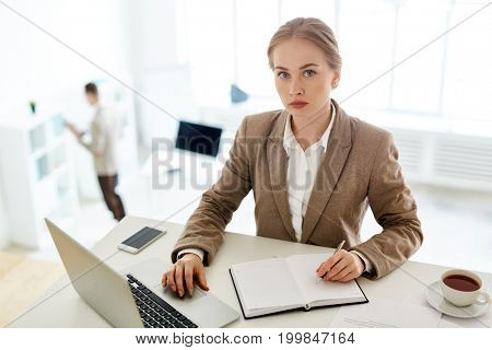 Portrait of pretty fair-haired white collar worker looking at camera confidently while taking notes before conducting important negotiations, interior of modern open plan office on background