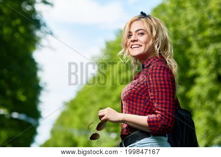 Cheerful blonde girl with sunglasses looking at camera while relaxing in amusement park