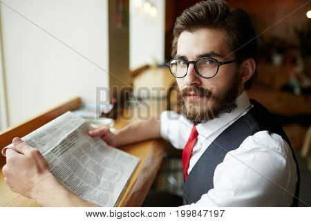 Elegant man in eyeglasses searching for vacancies in newspaper adverts
