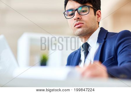 Serious man in suit and eyeglasses concentrating on work