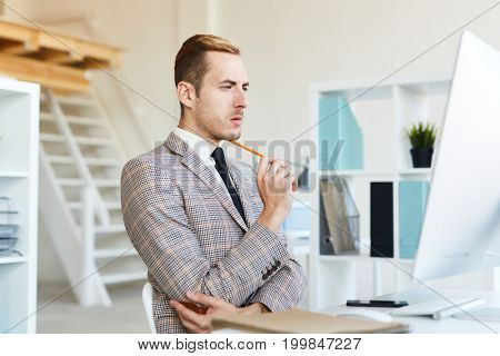 Profile view of pensive young financial manager with stylish haircut preparing annual accounts while sitting in front of computer at modern spacious office