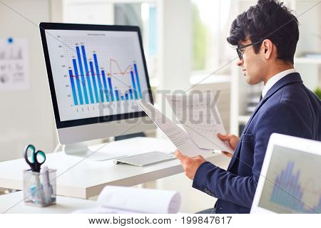 Businessman looking through papers by workplace and analyzing statistics