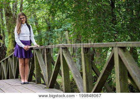 Beautiful Pretty Blonde School Girl Child Cheerfully Smiling With Glasses, White Shirt, Purple Skirt