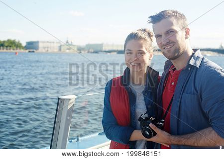 Young tourists with photocamera enjoying travel by water