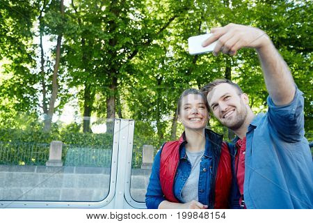 Young adventurers making selfie while traveling on steamer