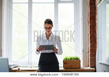 Young female in formalwear searching for data or job in the net