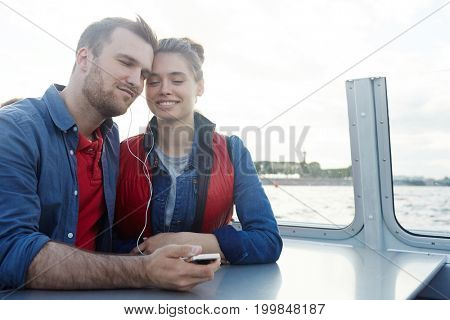 Restful couple listening to their favorite music during travel by steamer