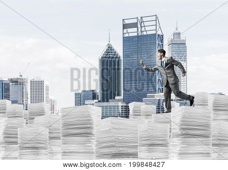 Businessman in black suit running with phone in hand on pile of documents with cityscape on background. Mixed media.