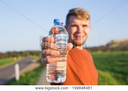 sporty man show bottle of water in a park.