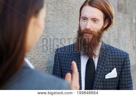 Well-dressed businessman with beard negotiating with partner