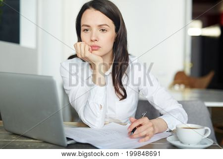 Pensive businesswoman deciding about pros and cons before signing new contract