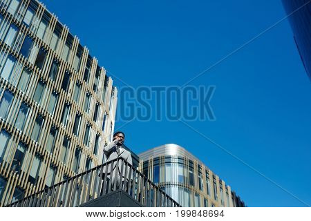 Professional banker or financier talking by smartphone against blue sky and modern architecture