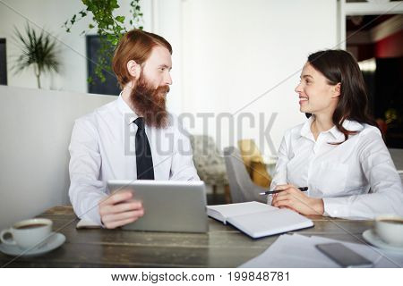 Two young designers having conversation at start-up meeting
