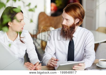Young broker listening to his client or colleague during appointment in cafe