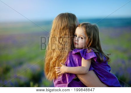 Mom hugging and holding her daughter. Beautiful young woman and her charming little daughter are hugging